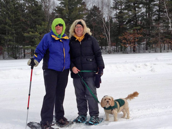 Winter fun! Friends snowshoeing along with their dog.