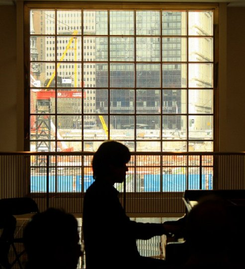 Pianist plays in front of a window that faces onto Ground Zero reconstruction