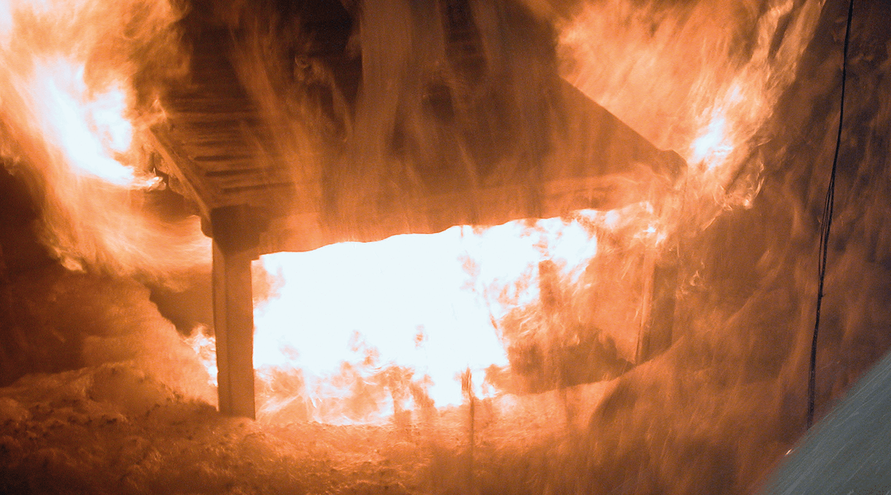 Figure 3 – The burning heptane pool when the foam has reached up to the edge of the locomotive's apertures and started to flow in. At lower application rates, the foam did not manage to get into the locomotive, with the filling rate falling to zero when the foam had reached part-way up the locomotive.