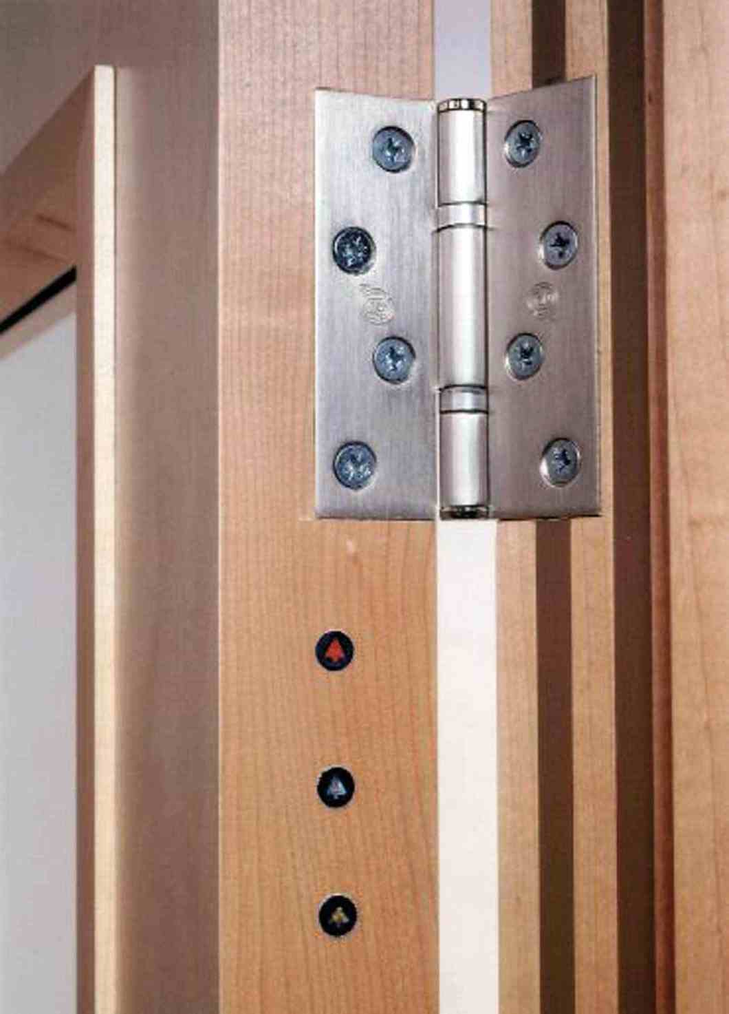 An example of a plugging system utilised by a third party certification provider for fire doors, denoting the door leaf and complete doorset has been manufactured by a third party certified company (red and silver plugs) and the doorset installed by a third party certified installer (gold plug).