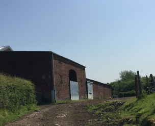 A similar view of the barns today. The majority of the bays in the barn have been lost over time, however this one still remains. Notice the decorative brick patterns on the wall. (Source: Own Photograph, 2016)