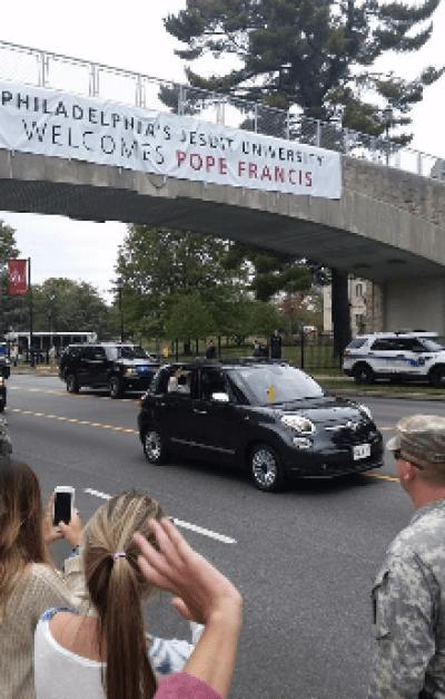 Pope Francis's Fiat approaches Saint Joseph's University.