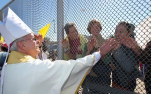 Bishop Seitz greets people on the Mexican side of the US-Mexico border during a bi-national mass in November 2014. [SOURCE: Catholic Herald]