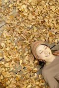 young-woman-happy-resting-on-leaves