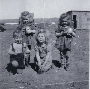 Fr. Frank making mud pies with his sisters - Vivian, Lillian, and Myrna - circa 1947.