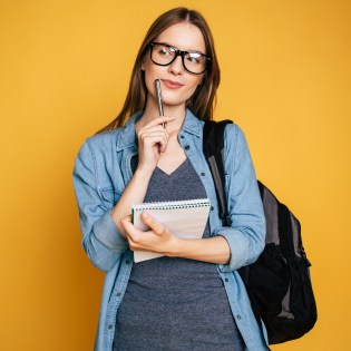 Happy and excited cute young student girl portrait in glasses with backpack isolated in studio