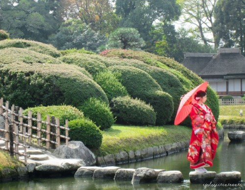 Donna in kimono passeggia nel giardino Korakuen, a Okayama