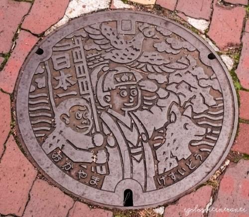 Tombino raffigurante Momotaro a Okayama