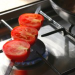 Grilling tomatoes over the gas hub