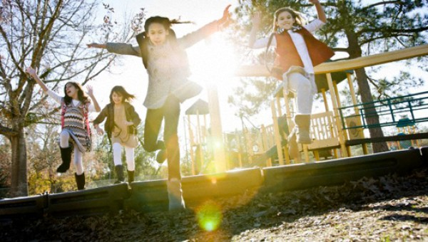 Girls (6-9) in playground with lens flare