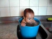 Малыш весело купается в ведре