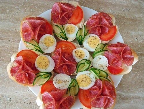 Нарезка из салями, овощей и яйца, поданная уже на кусочках хлеба