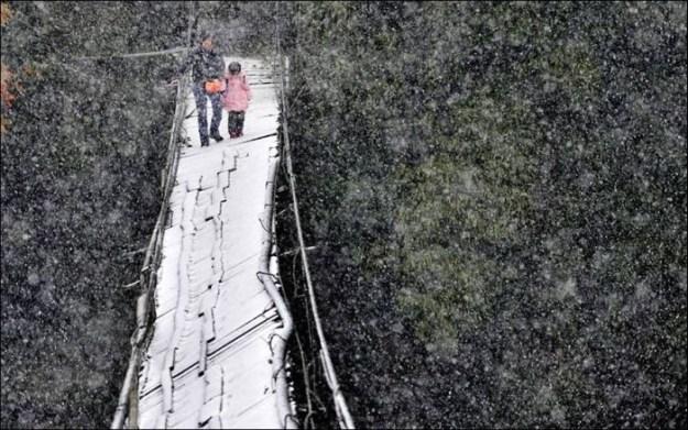 Опасный путь через сломанный мост, припорошенный снегом, в китайской провинции Сычуань