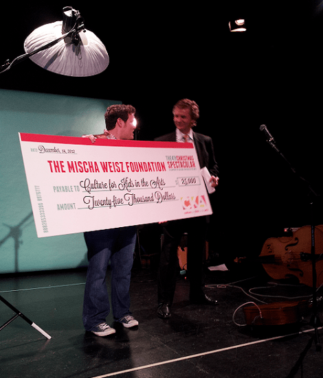 Chris Farias receiving the cheque from Frank Helt