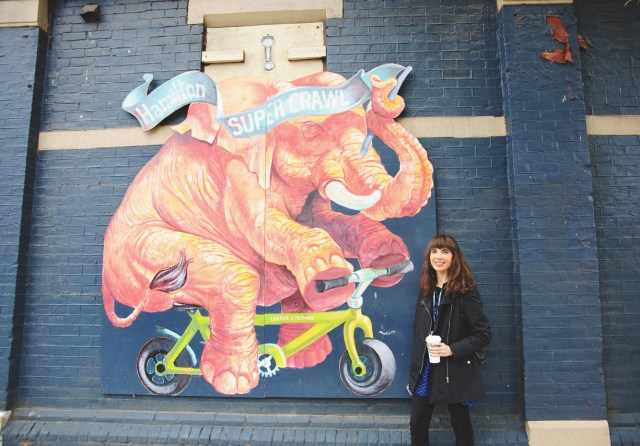 Kristin Archer on James Street North next to mural by Lester Coloma