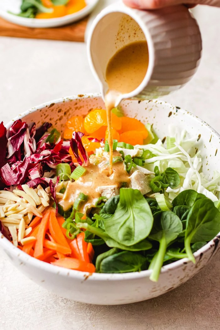 Image to show pouring the peanut salad dressing into a big salad bowl