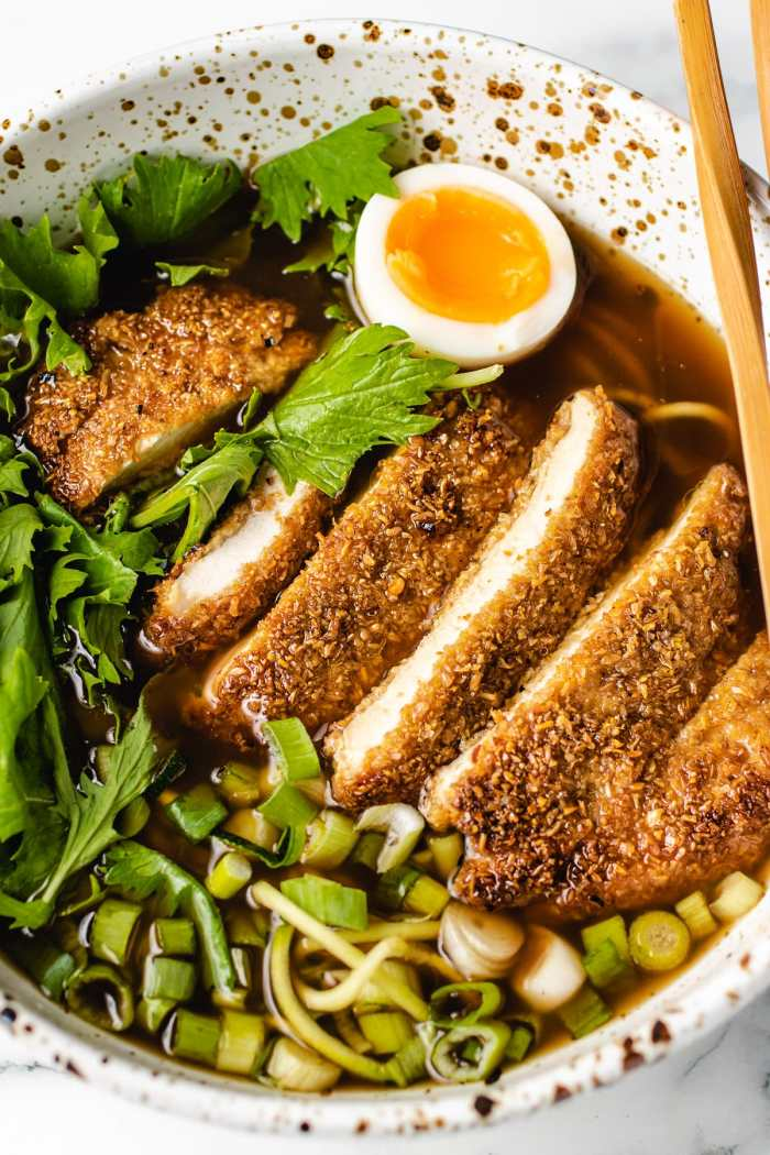 A side shot of katsu chicken in a ramen bowl soup