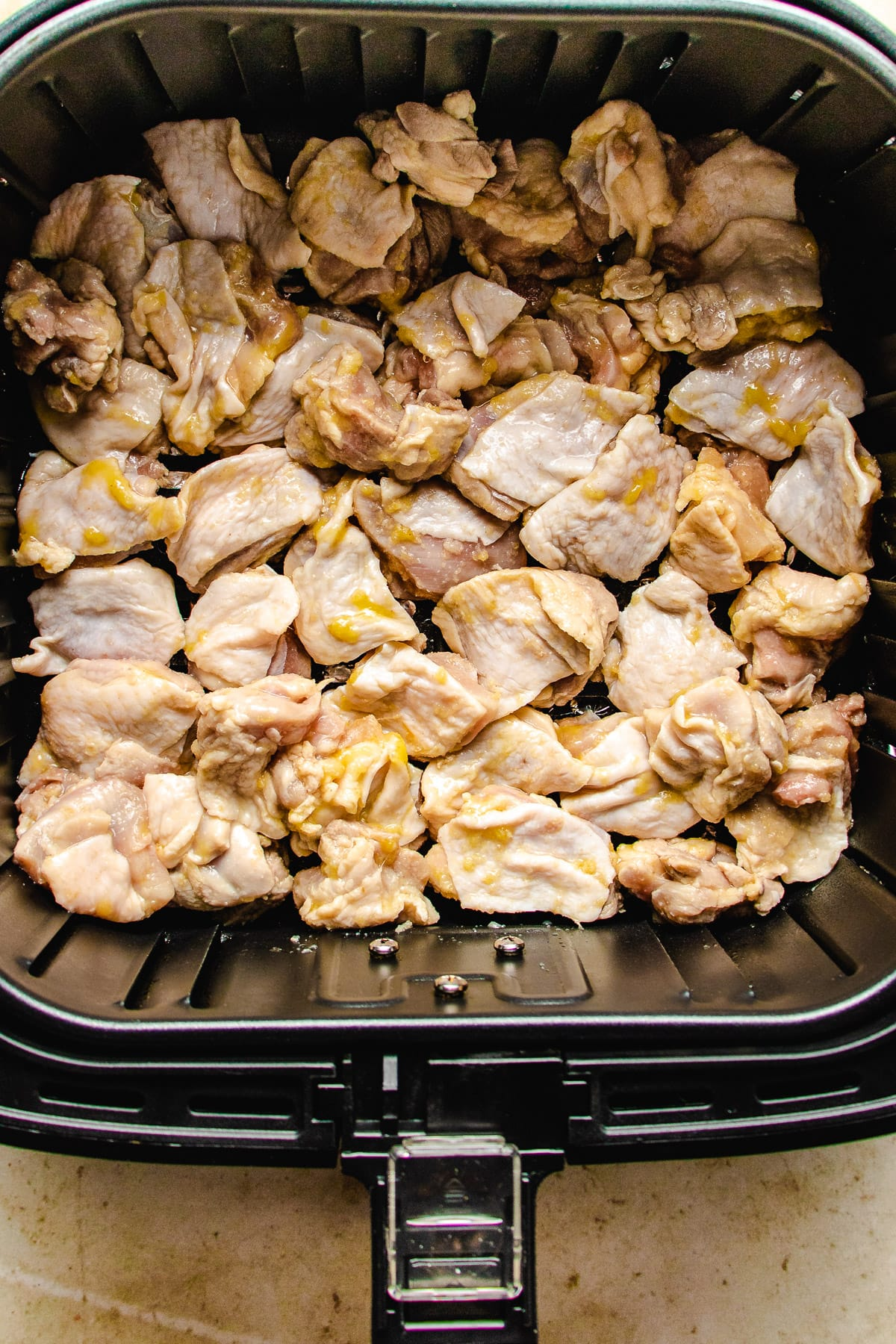 Place the marinated chicken thighs skin side up in the fryer basket