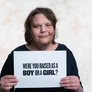 "In a photo for ABC, Alex holds a sign asking ""were you raised as a boy or girl?"