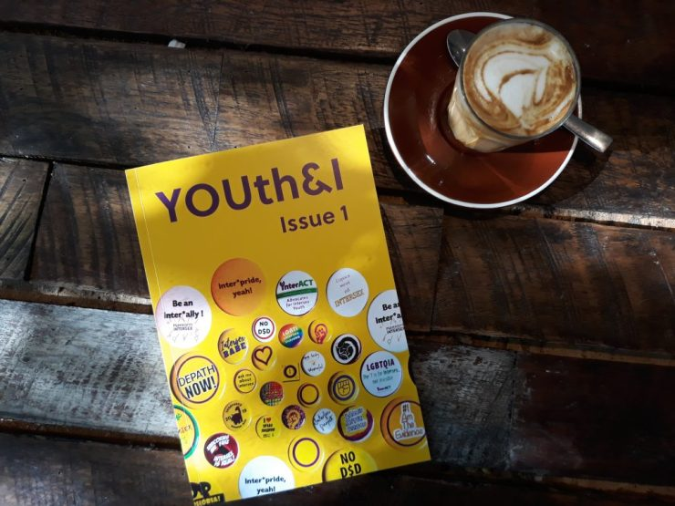 YOUth & I publication, on a wooden table, accompanied by a cup of coffee