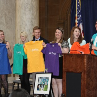 """IHSPA student officers display Mary Beth Tinker's more comical First Amendment shirts that coincide with their speech topics: Lauren Lecy, Chesterton High School (Speech); Ashley Shuler, Ben Davis High School (Petition); Nike Jordan, Portage High School (Assembly); Michelle Roberts, Greenwood High School (Religion); and Carley Lanich, Lawrence Central High School (Press). When keynote speaker Mary Beth Tinker and Mark Tague, Carmel High School, realize that the person who provides the introduction to the evening doesn't get a shirt they encourage Carley Lanich to share Freedom of the Press. Tinker, the popular icon of student expression, inspired students to """"stand up and speak up"""" and stayed after the event to talk to students who wanted to meet her."""
