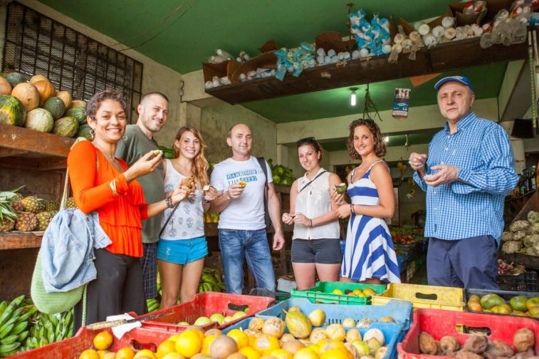 Spanish students trying fresh and exotic fruits on an educational tour with teacher Sheilla Camarena to the market in Sosua Los Charamicos