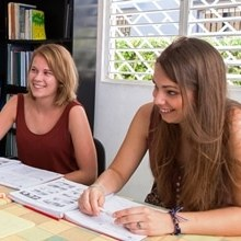 2 students sit in a classroom learning Spanish in their intensive course at IIC Spanish School in Santo Domingo which is also accredited for Bildungsurlaub.
