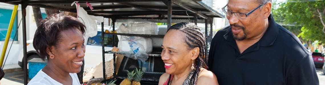 2 Spanish students with their teacher practice their Spanish at a fruit stand at IIC Santo Domingo and experience first-hand that immersion provides the fastest way to learn Spanish.
