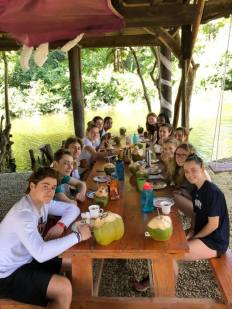 Spanish language students drink coco loco, a typical Dominican cocktail with rum served in a fresh coconut at Rugama Tours, chef Ruddy Martinez.
