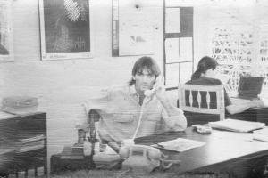 Thomas Fritsch, der Gründer der Sprachschule Casa Goethe IIC sitzt am Schreibtisch in der Schule auf einem alten Schwarz-Weiß-Foto.
