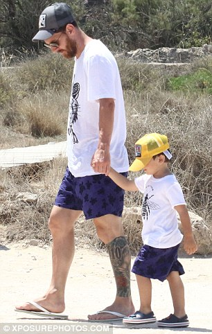 Matching Messi: Making the visit to land a special occasion, the footballer and Thiago appeared to coordinate their outifts, sporting matching swimming shorts, similar printed tees and caps