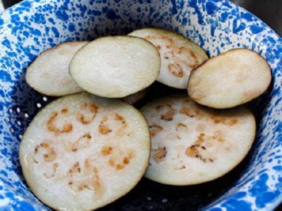Положите ломтики баклажана в дуршлаг и посыпьте их солью