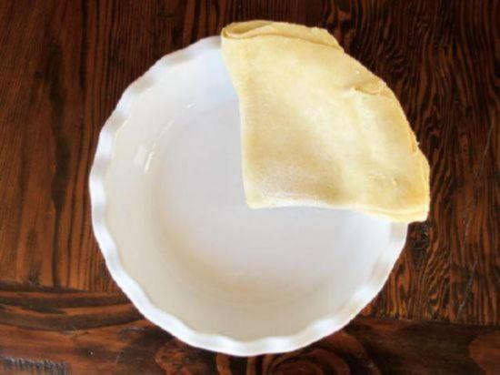 Положите свернутый лист теста в форму для выпечки