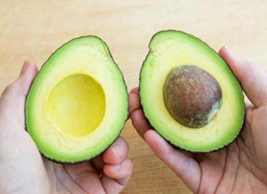 Разделите плод авокадо на две половинки, повернув их на встречу друг другу