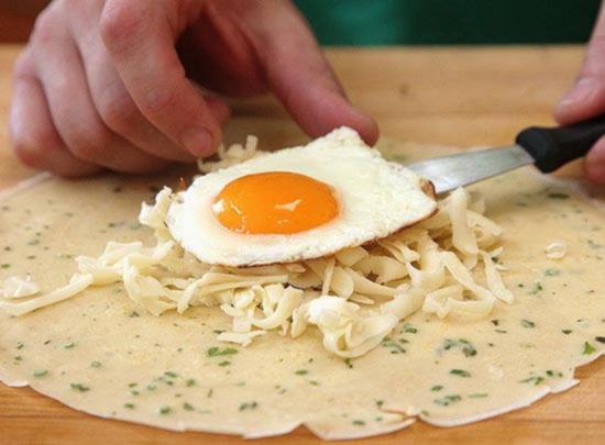 В центр блинчика положите натертый сыр ветчину и яйцо