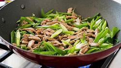 Подавайте жареную свинину с зеленым луком и чесноком как отдельное блюдо или гарнировав рисом.