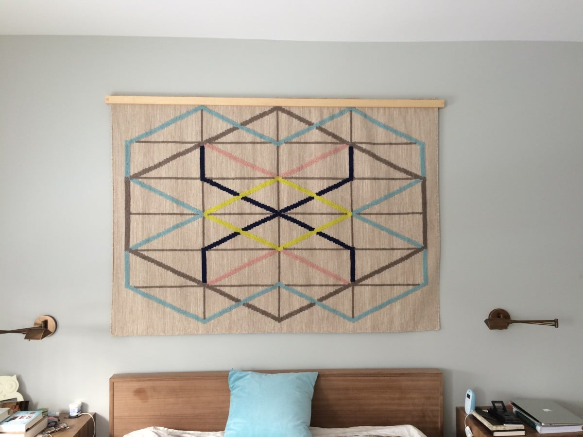 Creating a wood quilt hanger turns an IKEA rug into a wall