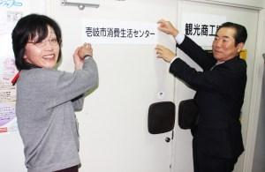 消費生活(看板を掲げる坂本委員(左))
