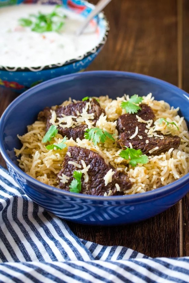 beef yakhni pulao in a blue bowl served with a side of raita