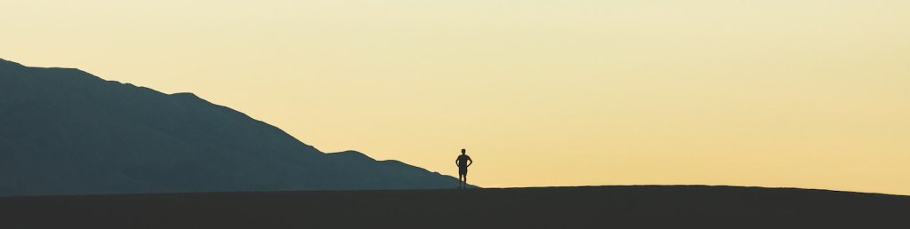 person's silhouette on horizon with mountains in background