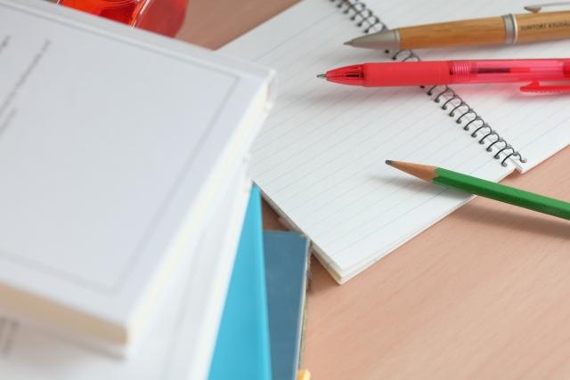 机の上に重ねられた本と,ノートや鉛筆