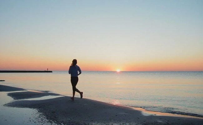 Woman Stretching And Preparing For Run On Beach Shot On