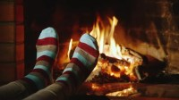 The Girl Warms His Feet By The Fireplace. Concept: Warmth ...