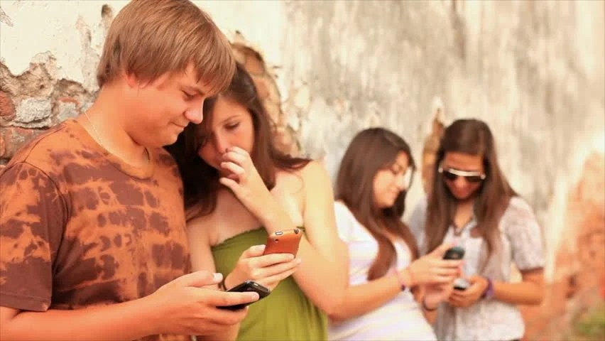 A Group Of Teenagers Hanging Out By An Old Brick Wall, Using Cell Phones To Send Text Messages And Talking To Each Other. Stock Footage Video ...
