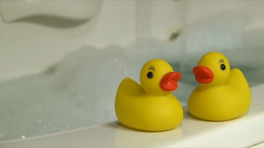 Rubber Duckies And Bubble Bath With Woman Stirring In Hot