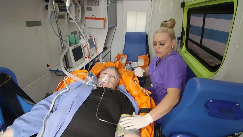Advanced Emergency Medical Technician Provide Critical Care To Patient In Ambulance Using