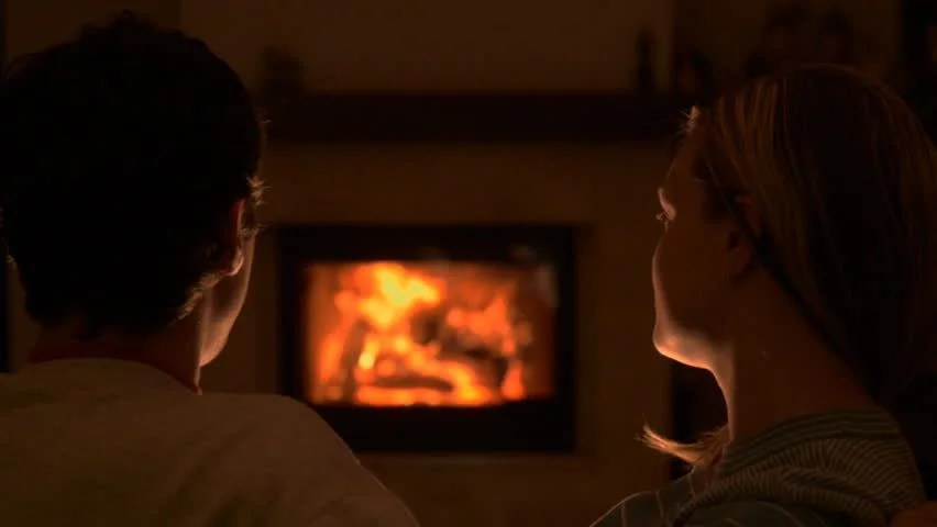 Couple Relaxing In Front Of Fireplace Man Looking At Woman Stock Girl Sitting Near The Fireplace And Leafing Through An