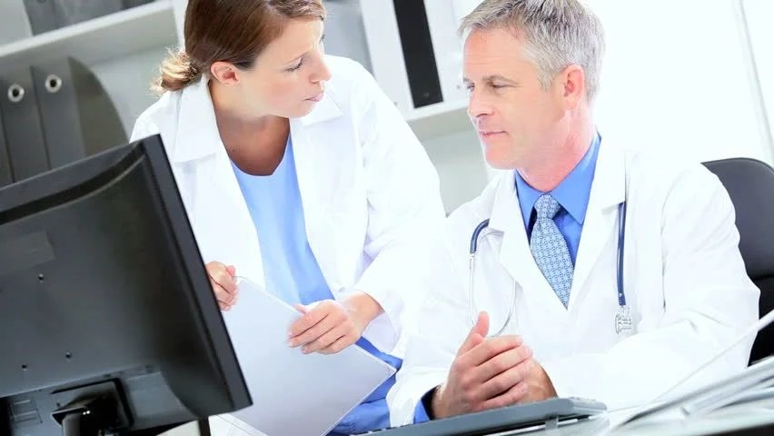 Clinical Nurse Discussing Patient Treatment With Male Consultant In Office Stock Footage Video