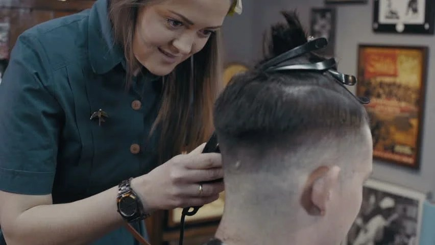 Woman Barber Cuts The Hair Of The Client With Clipper At Barbershop Slow Motion Stock Footage