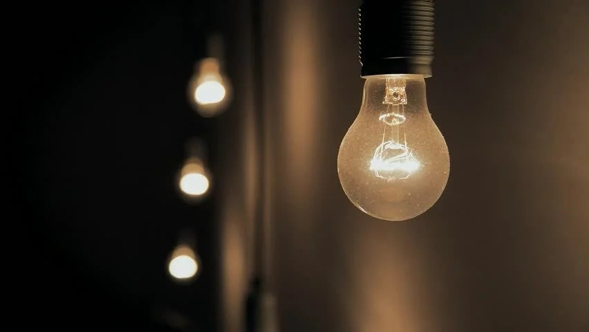 Lightbulb Flickers Against A Blue Wall Stock Footage Video